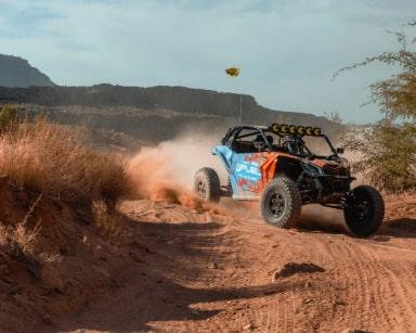 Orange and Blue UTV kicking up dust offroading