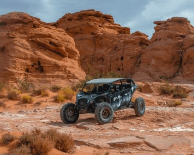 Can-Am Maverick X3 parked in front of rock formations in the desert