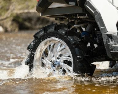Silver UTV Tire in a shallow stream