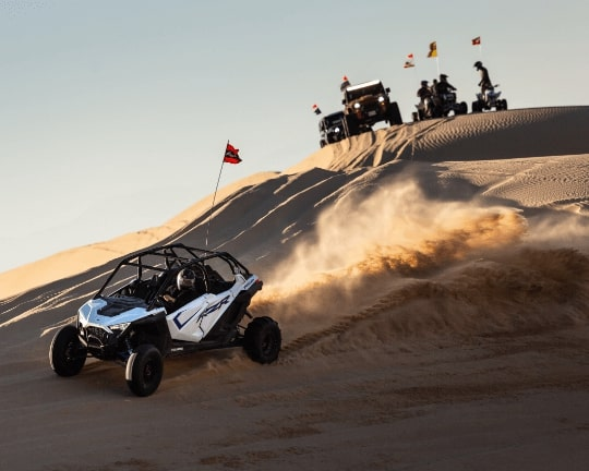 White Polaris RZR Pro XP UTV driving down a sand dune with Jeeps and ATVs in the backround