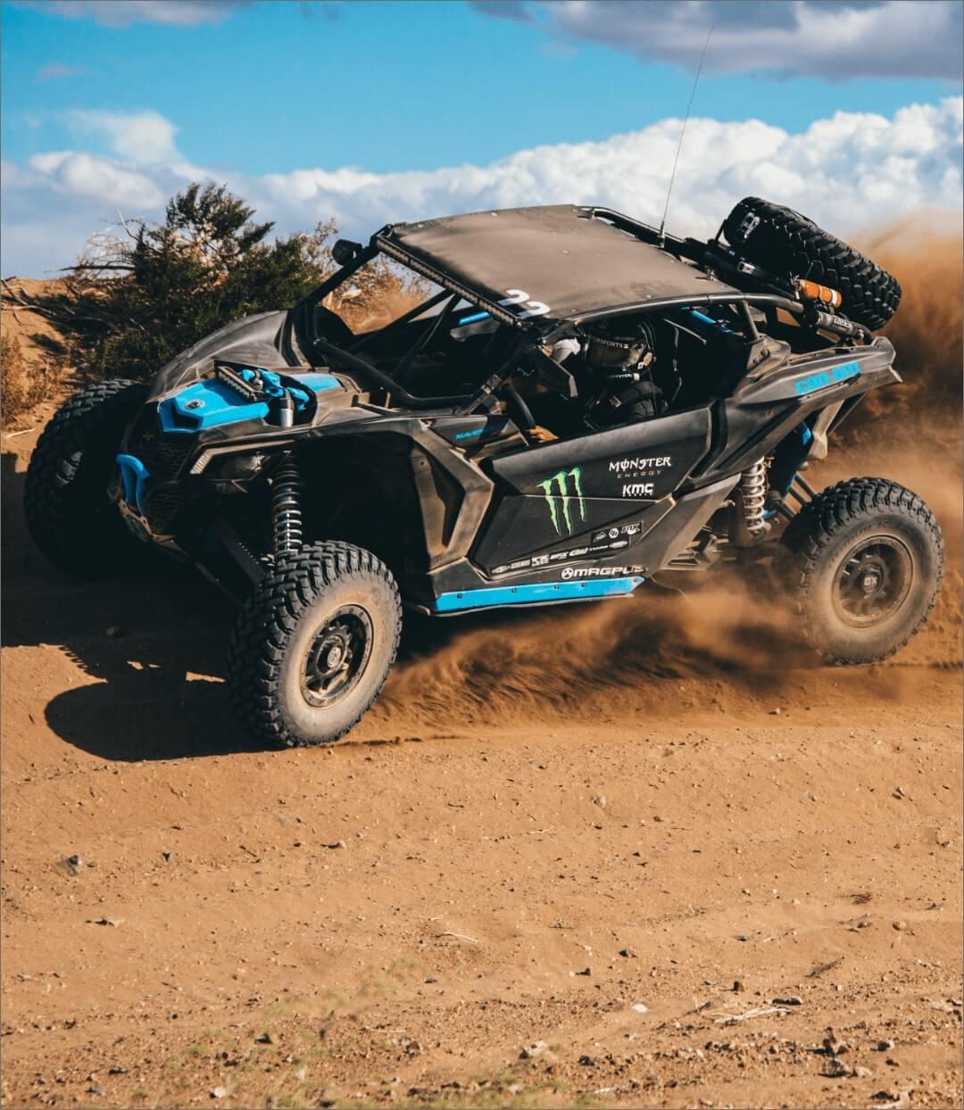 Black and Blue Can-Am Maverick X3 UTV kicking up dirt on a track