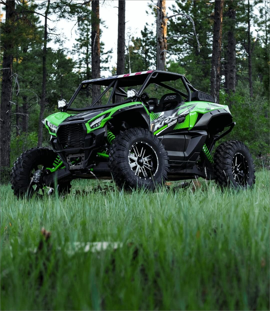 Green and Black Kawasaki Teryx KRX 1000 parked in the woods