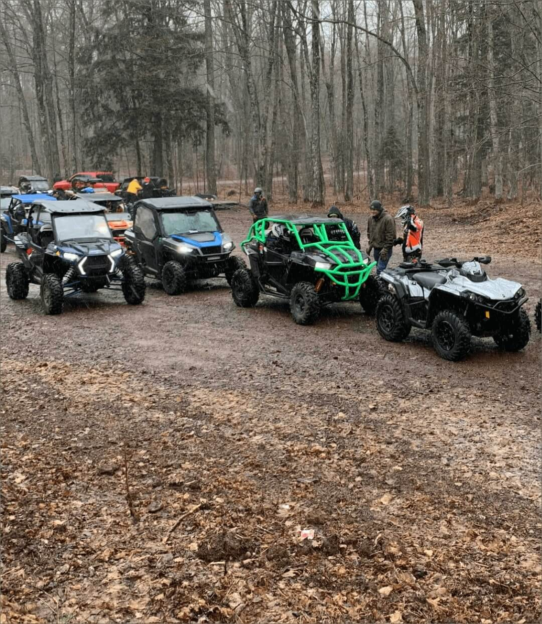Many ATVs and UTVs with their drivers in the woods while raining